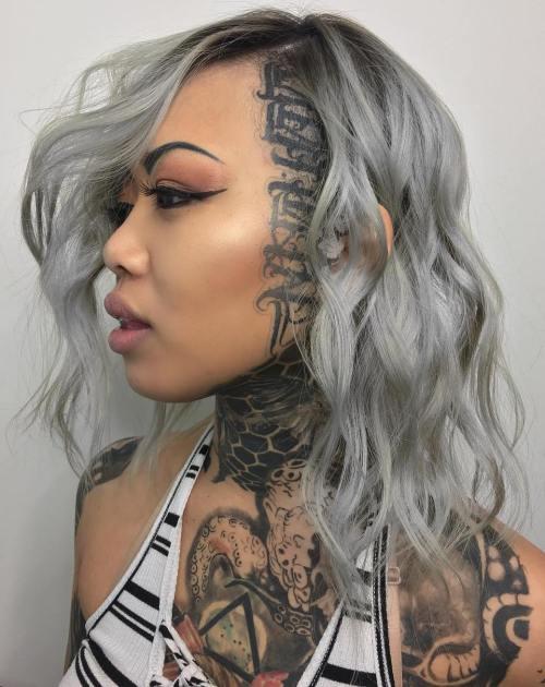Medium wavy gray hairstyle with head tattoo